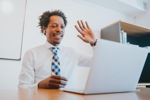 Professioneller geschäftsmann in einem virtuellen meeting per videoanruf mit laptop im büro. unternehmenskonzept.