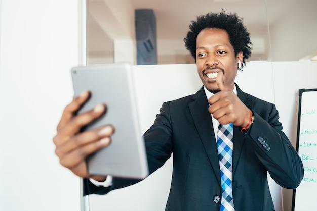 Professioneller geschäftsmann in einer virtuellen besprechung auf videoanruf mit digitalem tablet im büro
