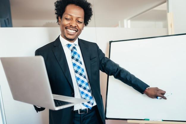 Professioneller geschäftsmann in einer virtuellen besprechung auf videoanruf mit laptop im büro. unternehmenskonzept.