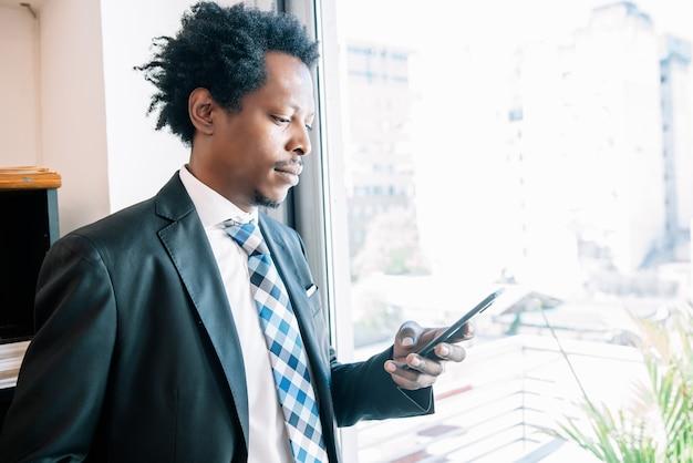 Professioneller geschäftsmann mit seinem handy während der arbeit im büro