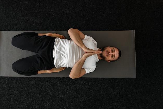 Professioneller glücklicher junger mann, der yoga macht und drinnen glücklich lächelt. meditation und entspannung.