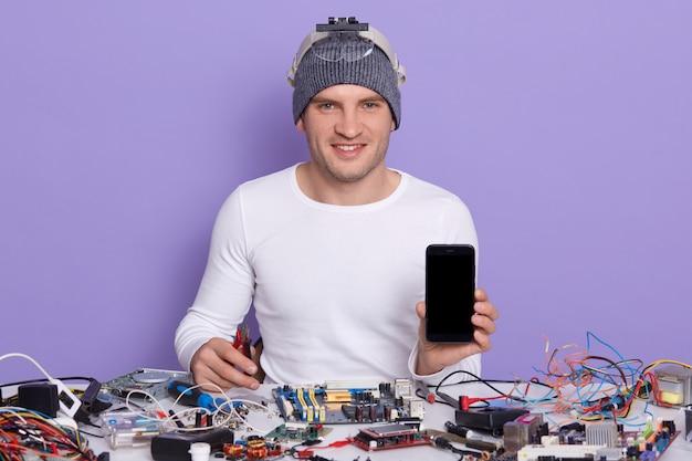 Professioneller handwerker, der kaputtes smartphone repariert und leeren bildschirm mit kopierraum für werbung zeigt