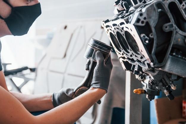 Professioneller handwerker in schwarzer schutzmaske arbeitet mit kaputten automotoren