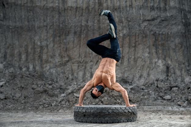 Professioneller hemdloser bodybuilder-trainingshandstand auf einem großen schwarzen rad im sandsteinbruch. junger mann im schwarzen medizinischen maskentraining im freien während der quarantänezeit.