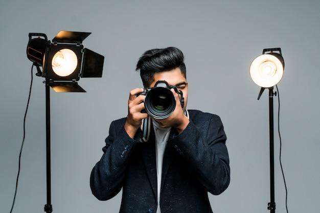Professioneller indischer junger fotograf, der fotos im studio mit leight macht