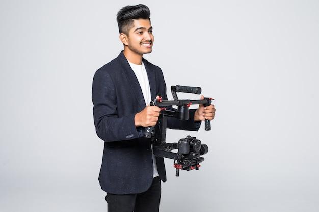 Professioneller indischer mann videograf mit gimball video slr ronin isoliert auf studio hintergrund