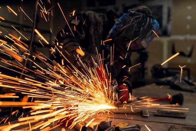 Professioneller industriearbeiter mit schutzmaske, der mit elektrischem schleifer und vielen funken in einer stoffwerkstatt arbeitet