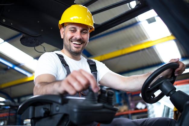 Professioneller industriefahrer, der eine gabelstaplermaschine im lager der fabrik bedient