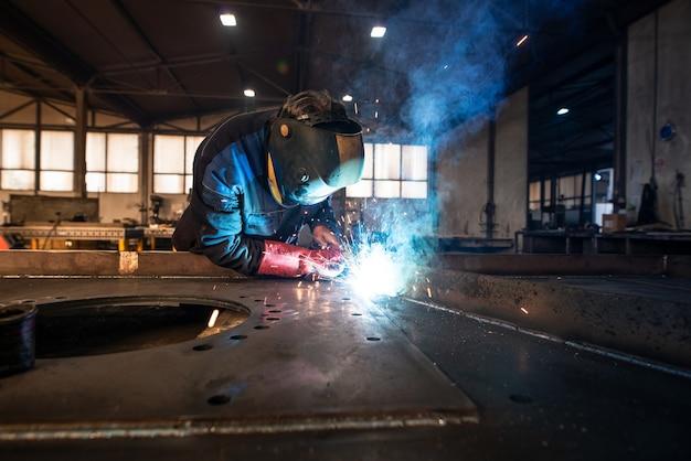 Professioneller industrieller schweißer, der metallteile in der metallbearbeitungsfabrik schweißt