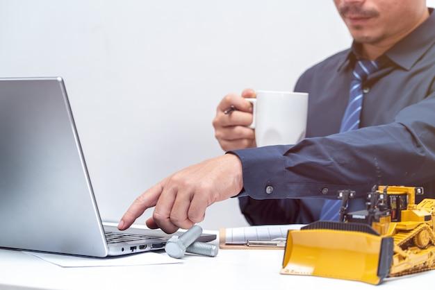 Professioneller ingenieur, der die hand zum laptop für während des arbeitstages im büro erreicht, repariert wartung schweres maschinenkonzept