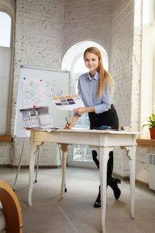 Professioneller innenarchitekt oder architekt, der mit farbpalette, raumzeichnungen im modernen büro arbeitet. junges weibliches modell, das zukünftige wohnung oder haus plant, farben und ableitung wählend.