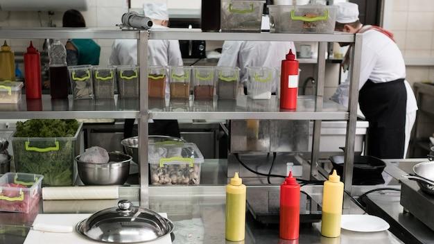 Professioneller innenraum der restaurantküche mit regalen voller waren, lebensmittel, saucen und gewürze