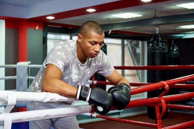 Professioneller junger boxer, der auf den seilen des ringes nach dem kampf stillsteht.
