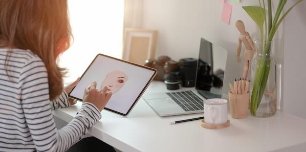 Professioneller junger grafikdesigner, der ihr projekt auf tablette an modernem arbeitsplatz bearbeitet
