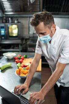 Professioneller junger koch in uniform und schutzmaske, der sich über den küchentisch beugt und online-rezepte auf dem laptop-display durchsieht