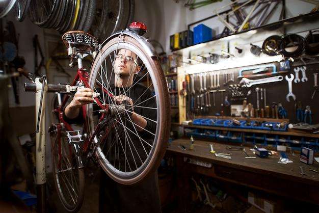 Professioneller junger mann, der fahrrad in der werkstatt putzt.