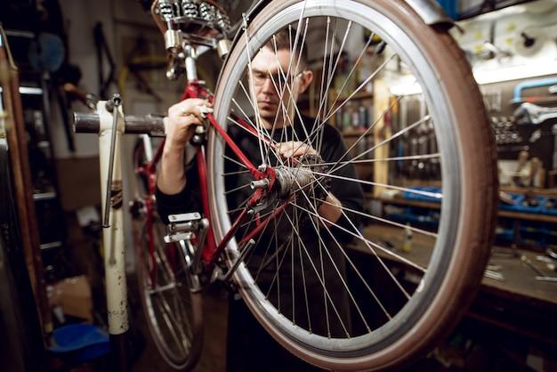 Professioneller junger mann, der fahrradheckstange in der werkstatt reinigt.