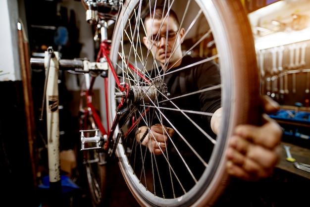 Professioneller junger mann, der fahrradraddrähte fest einstellt.