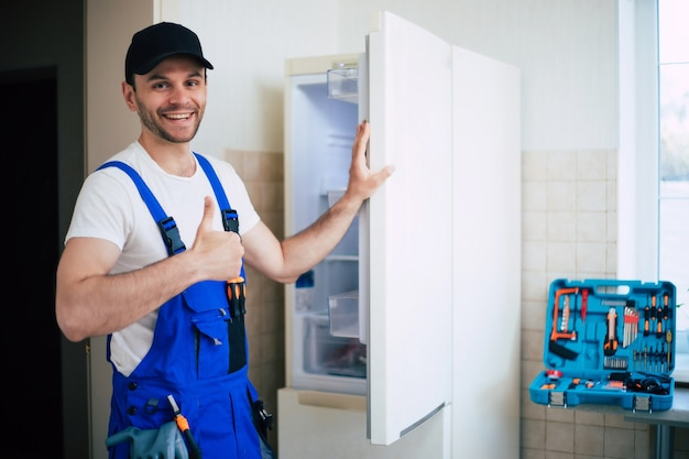 Professioneller junger mechaniker in arbeiteruniform und mütze mit modernem werkzeugkasten mit ausrüstung nach der reparatur des kühlschranks in der küche