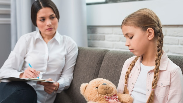 Professioneller junger psychologe, der versucht, zum mädchen mit problemen durchzukommen