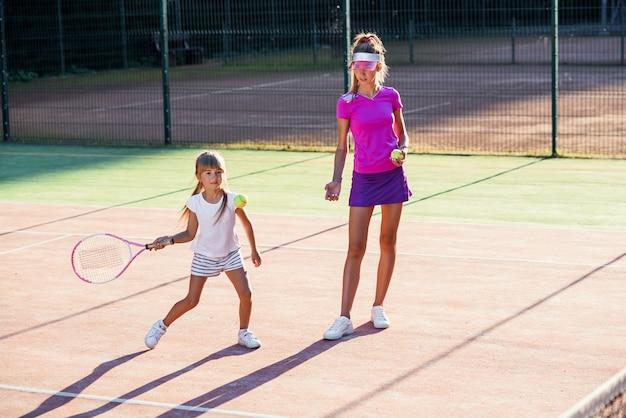 Professioneller junger trainer wirft ball und kleiner tennisspieler schlägt ball durch schläger während des trainings auf dem außenplatz. sport, gesundheitskonzept.