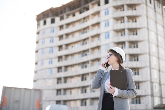 Professioneller junger weiblicher architekt, der auf dem mobiltelefon hält klemmbrett an der baustelle spricht