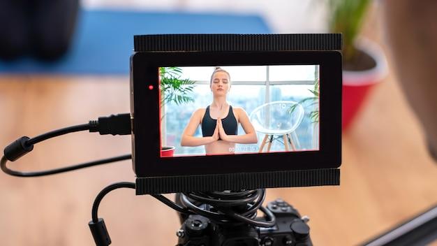 Professioneller kameramann mit kamera und externem display, der eine junge blonde frau aufzeichnet