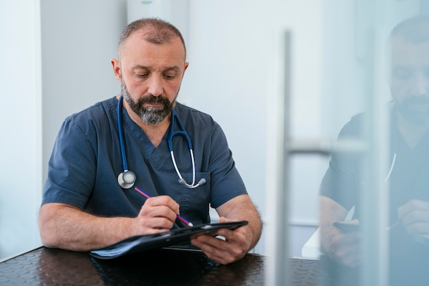 Professioneller kardiologe, der einen ordner mit stethoskop hält. nahaufnahme und detail.