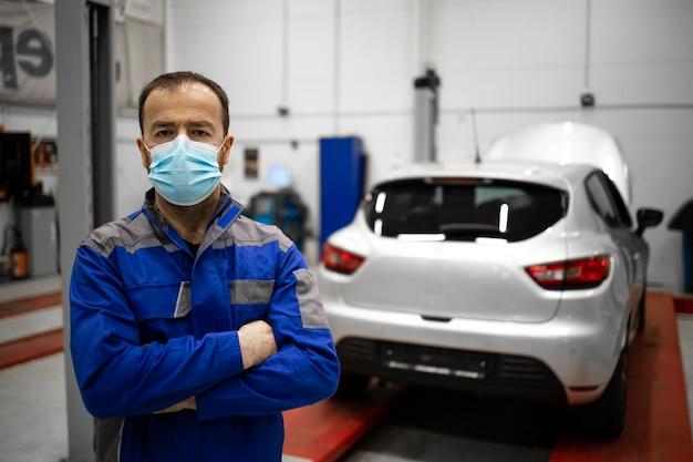 Professioneller kaukasischer automechaniker, der schutzgesichtsmaske in der fahrzeugwerkstatt während der koronavirus-pandemie trägt.