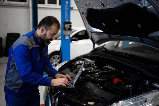 Professioneller kaukasischer automechaniker mittleren alters mit laptop-computer-diagnosewerkzeug, das durch fahrzeugmotorbereich mit offener motorhaube steht und fehlfunktion erkennt.