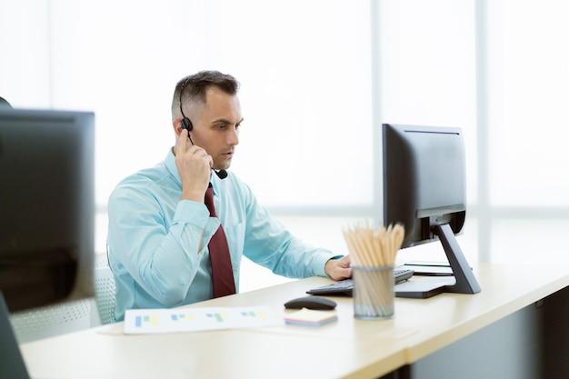 Professioneller kaukasischer helpdesk-beauftragter, der im büro arbeitet, helpdesk-beauftragter, der mit dem kunden am telefon spricht. westlicher junger mann, der im büro arbeitet.