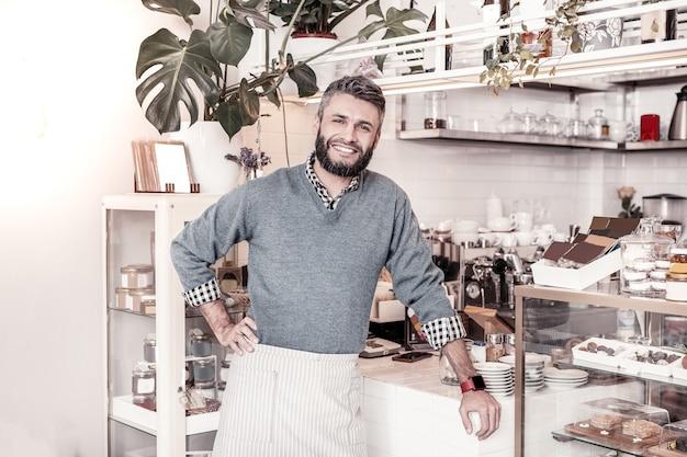 Professioneller kellner. angenehmer fröhlicher mann, der in der bäckerei steht, während er in der cafeteria arbeitet