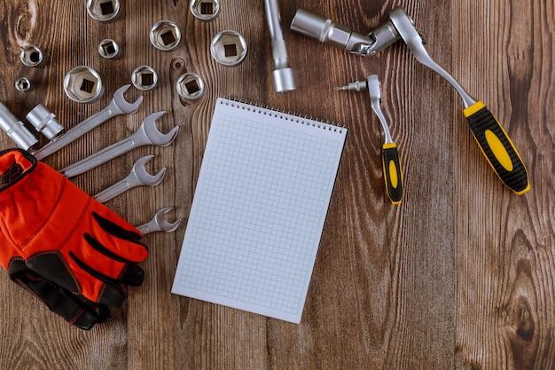 Professioneller kfz-werkzeugsatz aus schraubenschlüsseln aus chromwerkzeugen mit spiralförmigen notizblock-schutzhandschuhen.
