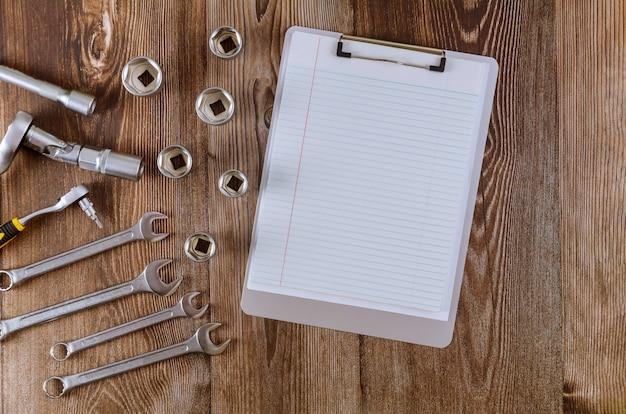 Professioneller kfz-werkzeugsatz mit schraubenschlüsseln aus chromwerkzeugen mit notizblock.