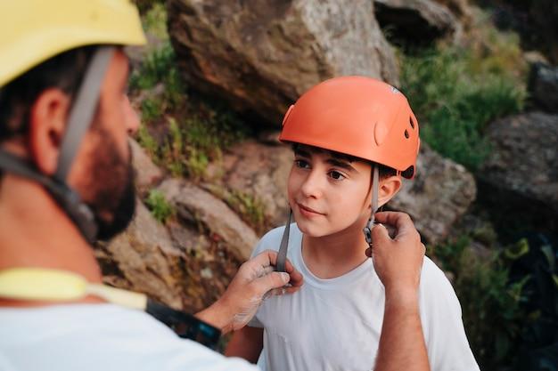 Professioneller kletterer bereitet seinen schüler darauf vor, beim klettern sicher zu sein