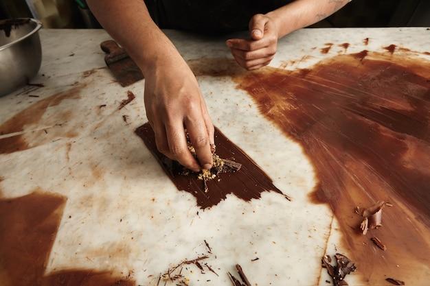 Professioneller koch arbeitet mit geschmolzener hausgemachter schokolade