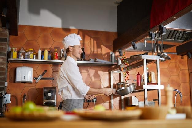 Professioneller koch, der in der küche kocht