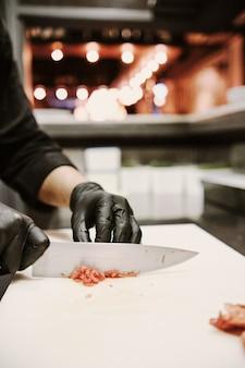 Professioneller koch, der rohes fleisch mit messer schneidet.