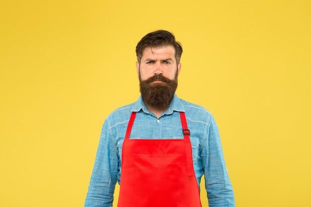 Professioneller koch in roter schürze. restaurantpersonal gesucht. kochen ist sein hobby. bärtiger mann in kochuniform. selbstbewusste männliche haushälterin. inhaber eines kleinen ladens. reife verkäuferin.