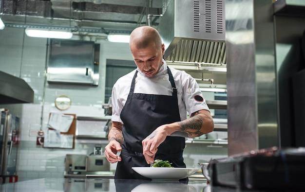 Professioneller koch in schwarzer schürze, der sein gericht auf dem teller garniert, während er in der restaurantküche arbeitet