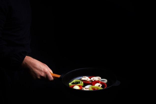 Professioneller koch. kocht gemüse in einer pfanne, asiatische küche. leckeres gesundes essen