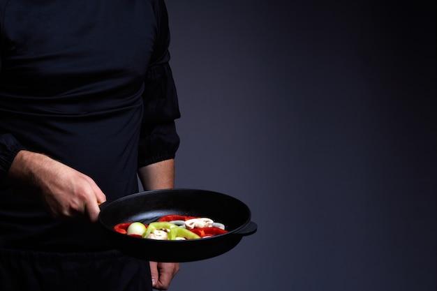 Professioneller koch. kocht gemüse in einer pfanne, asiatische küche. rezeptbuch. leckeres gesundes essen