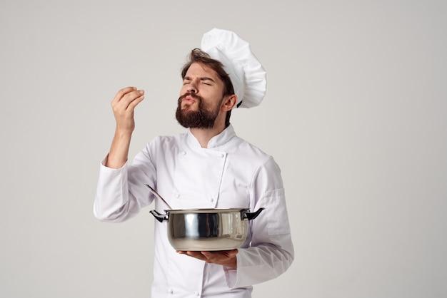 Professioneller koch mit einem topf in der hand, der die kocharbeit von speisen versucht
