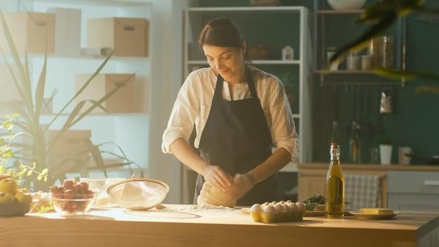 Professioneller koch streut mehl und knetet teig auf einem holztisch in einer modernen wohnküche