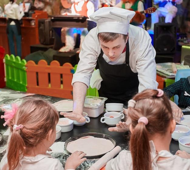 Professioneller koch zeigt pizzaboden, auf meisterkurs für kinder