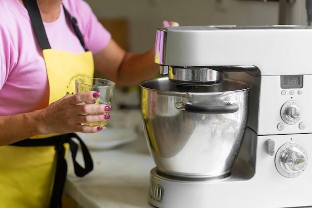Professioneller konditor der frau, der ein dessert vorbereitet. fügt zutaten hinzu und mischt den teig in einem mixer
