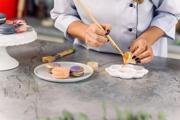 Professioneller konditor, der lebensmittel in goldfarbe zum malen von frischen macarons zubereitet.