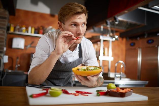 Professioneller küchenchef, der scharfes essen probiert