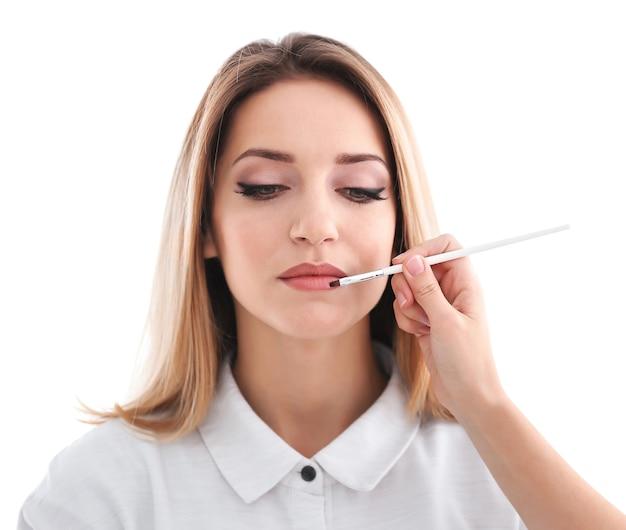 Professioneller künstler, der make-up für modell auf weiß erstellt