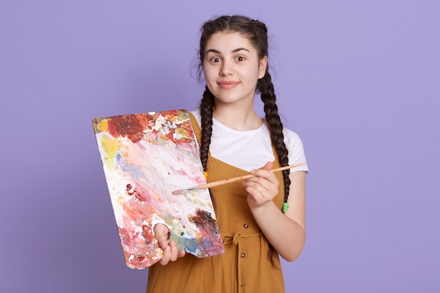 Professioneller künstler, der mit pinsel und palette lächelt